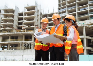Business partners discussing a blueprint of the building at the construction site