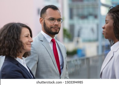 Business partners discussing contract outside. Multiethnic business man and women standing in city street and talking. Meeting outside concept