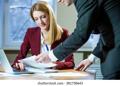 Business partners discussing documents and ideas at meeting in office. Sharing experience with colleague. Man and woman in suits working together with papers and laptop.