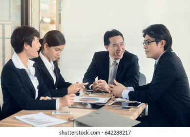 business partners discussing documents and ideas at meeting in an office