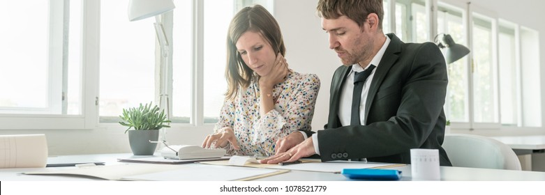 Business partners doing calculations on an adding machine or calculator, conceptual of accounting.