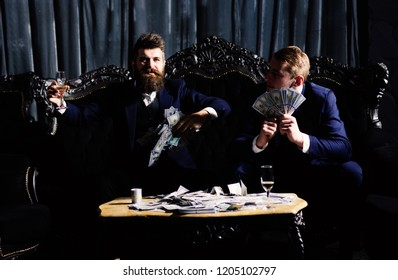 Business partners, elite, superior persons wasting money in club. Man throwing cash, money, banknotes. Luxury life concept. Men in suit, businessmen sit in dark luxury interior background.