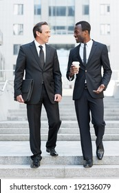 Business partners. Full length of two cheerful business men talking while moving down by staircase