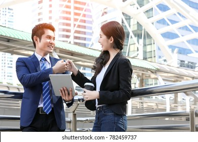 Business Partners Giving Fist Bump after complete a deal on cityscape background. Happy Successful Teamwork Partnership closing the deal. Businessman with tablet giving fist bump to businesswoman.