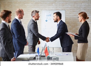 Business partners handshaking a deal at office