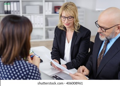 Business partners, a middle-aged man and woman, conducting a job interview reading the female applicants CV with serious expressions