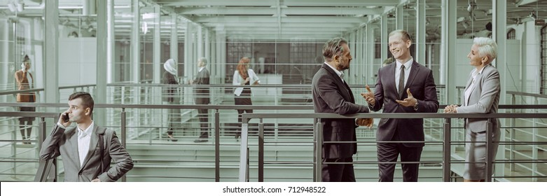 Business partners negotiating in modern interior, panorama