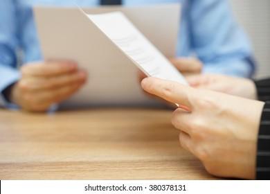 Geschäftspartner, die Rechtsdokumente lesen und verhandeln