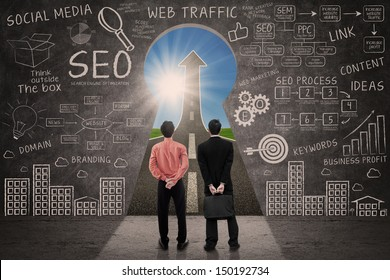 Business partners and SEO doodle on blackboard with success road view