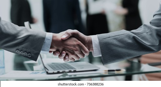 business partners shake hands after a meeting on the background
