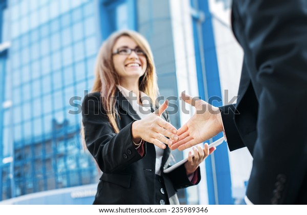Business partners shake hands, standing in front of his office.
