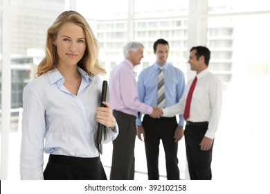Business Partners shaking hands in the background and beautiful businesswoman looking at camera on foreground