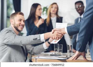 business partners shaking hands with blurred colleagues on background