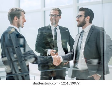 business partners shaking hands in the lobby of the business cen
