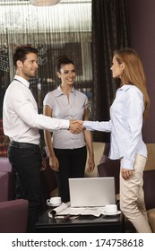 Business partners shaking hands at meeting in hotel lobby or bar.
