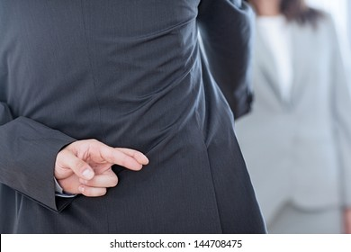 Business partners shaking hands with one of them holding her fingers crossed behind her back.