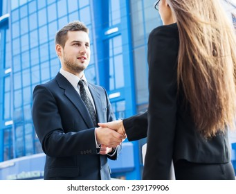Business partners shaking hands, standing in front of his office.
