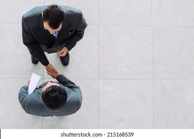 Business partners shaking hands as a symbol of unity, view from the top
