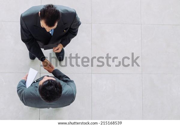 Geschäftspartner, die sich als Symbol der Einheit die Hände schütteln, von oben aus