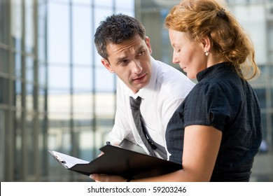 Business partners signing contract outdoors. Red-haired woman trying to prove his business partner in newly created business strategy in front of office building.