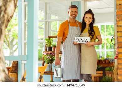 Business partners. Smiling couple standing on the porch of the flower shop they are opening.