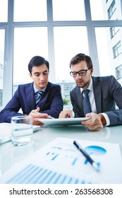 Business partners studying data in office