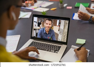 Business partners talking through video call. Back view of african businessman in office doing video chat calling a client. Young man and his business colleague talking to each other through a video.