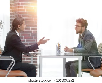 business partners talking while sitting at your Desk