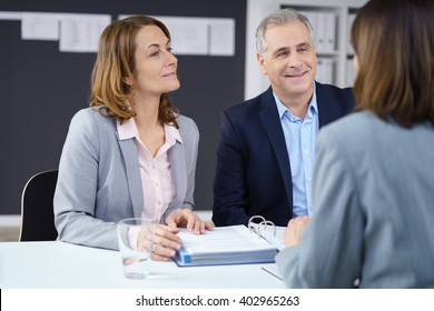 Business partners or team in a meeting sitting together around an office table discussing paperwork, focus to a smiling middle aged man and woman