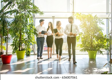 Business partners walking down in office building and talking.