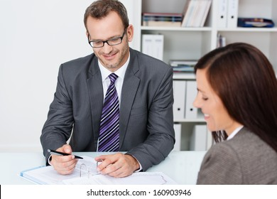 Business partners at work in the office with focus over the shoulder of a woman to a smiling confident businessman in glasses working on paperwork