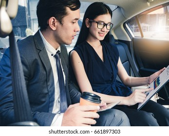 Business partners working in the back seat in the car