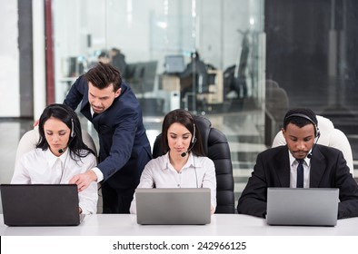 Business partners are working with their manager in a call center.