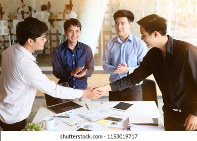 Business Partnership concept. businessman shaking hands finishing up a meeting four colleagues successful startup business talking.