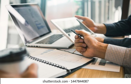 Business partnership coworkers using a tablet to chart company financial statements report and profits work progress and planning in office room.