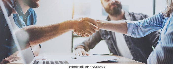 Business partnership handshake concept.Photo two coworkers handshaking process.Successful deal after great meeting.Horizontal, blurred background.Wide