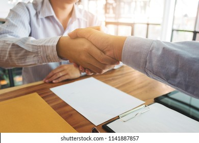 Business partnership handshake discussing agreement contract.