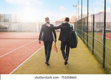 Business, partnership, sport. Back view successful businessman walking, chatting while tapping partner on shoulder, wearing suits and tennis equipment.  Business partners practicing sport. Mentoring.
