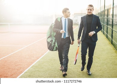 Business, partnership and sport. Front view successful businessman walking and chatting after a tennis set, wearing suits and tennis equipment.  Business partners practicing sport together. Mentorin