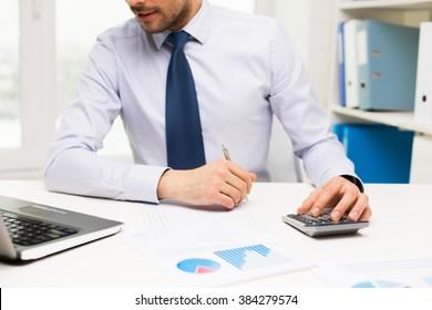 business, people, accounting and technology concept - close up of businessman with laptop computer, calculator and papers working in office