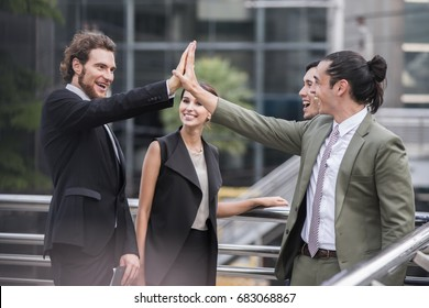 Business, People, Advertisement concept - Successful group of Confident business people and business team making a high five in outdoor meeting.