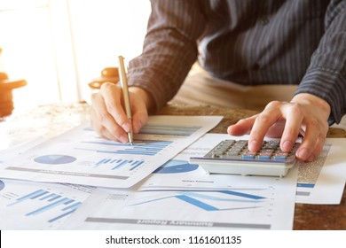 business people analyzing graph and chart document on office desk