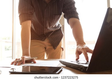 business people analyzing graph and chart document with laptop computer on office desk