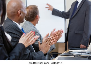 Business people applauding after speech of a businessman at the conference