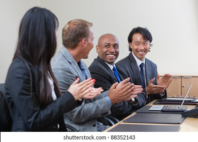 Business people applauding and smiling in presentation room
