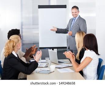 Business People Appreciating Businessman Explaining In Presentation