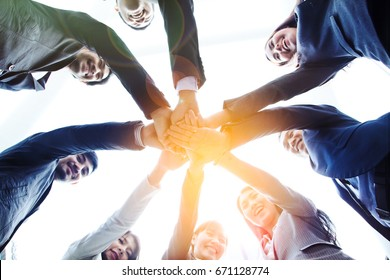 Business People Asia bottom view of join hands put together, looking down at camera, team of happy smiling, achieve success together, successful business plan, Corporate Meeting Teamwork Concept.