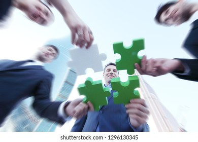 Business people assembling jigsaw puzzle near skyscrapers