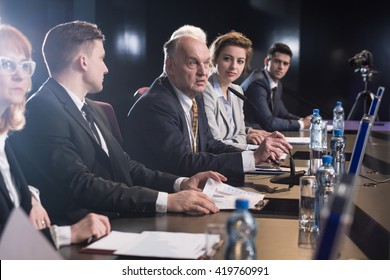 Business people attending seminar, debate or conference