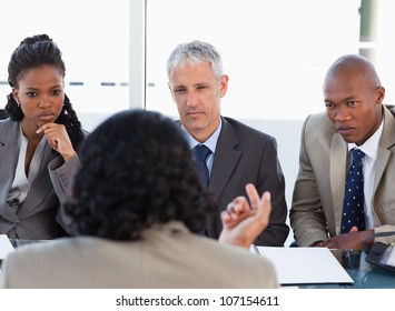 Business people attentively listening to a serious speaker in a meeting